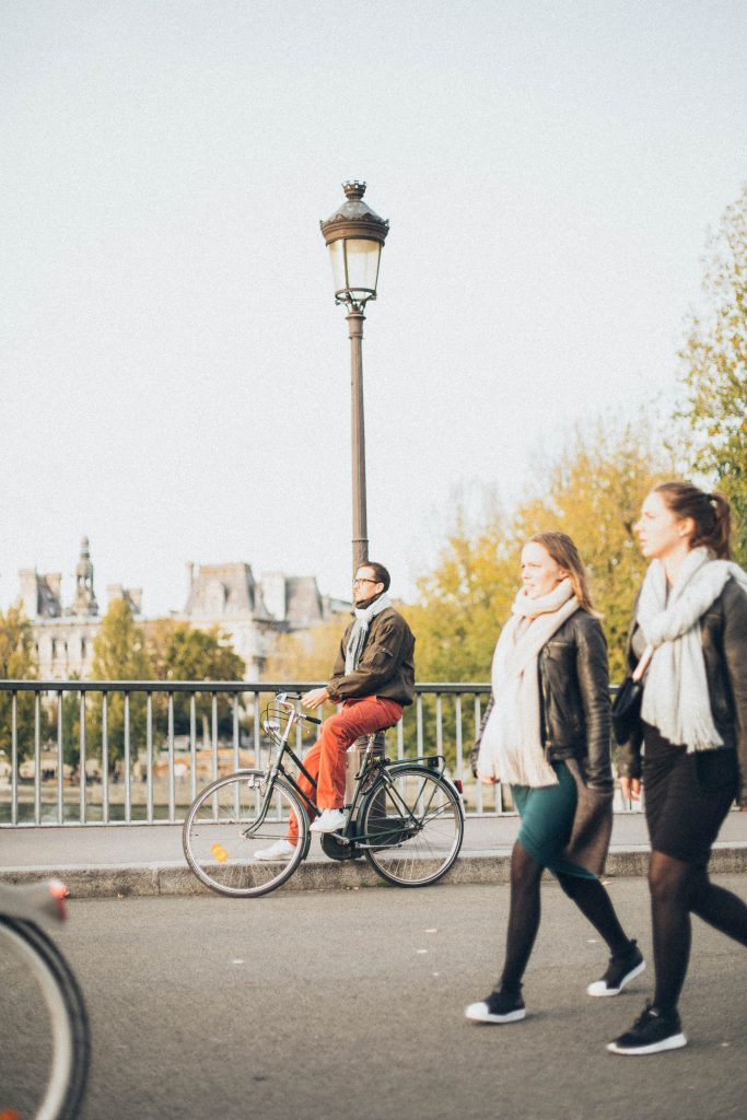People walking and riding bikes in a city; Photo by Elina Sazonova of Pexels
